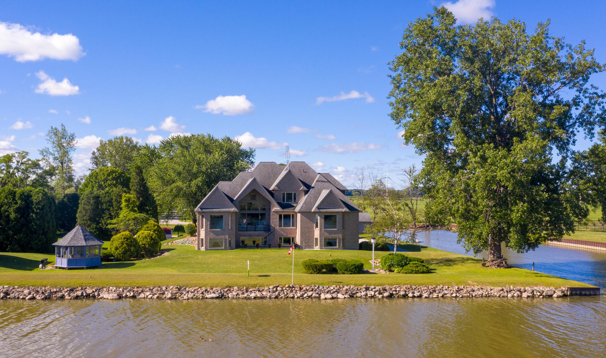 Exterior of large house, spacious backyard facing water-way