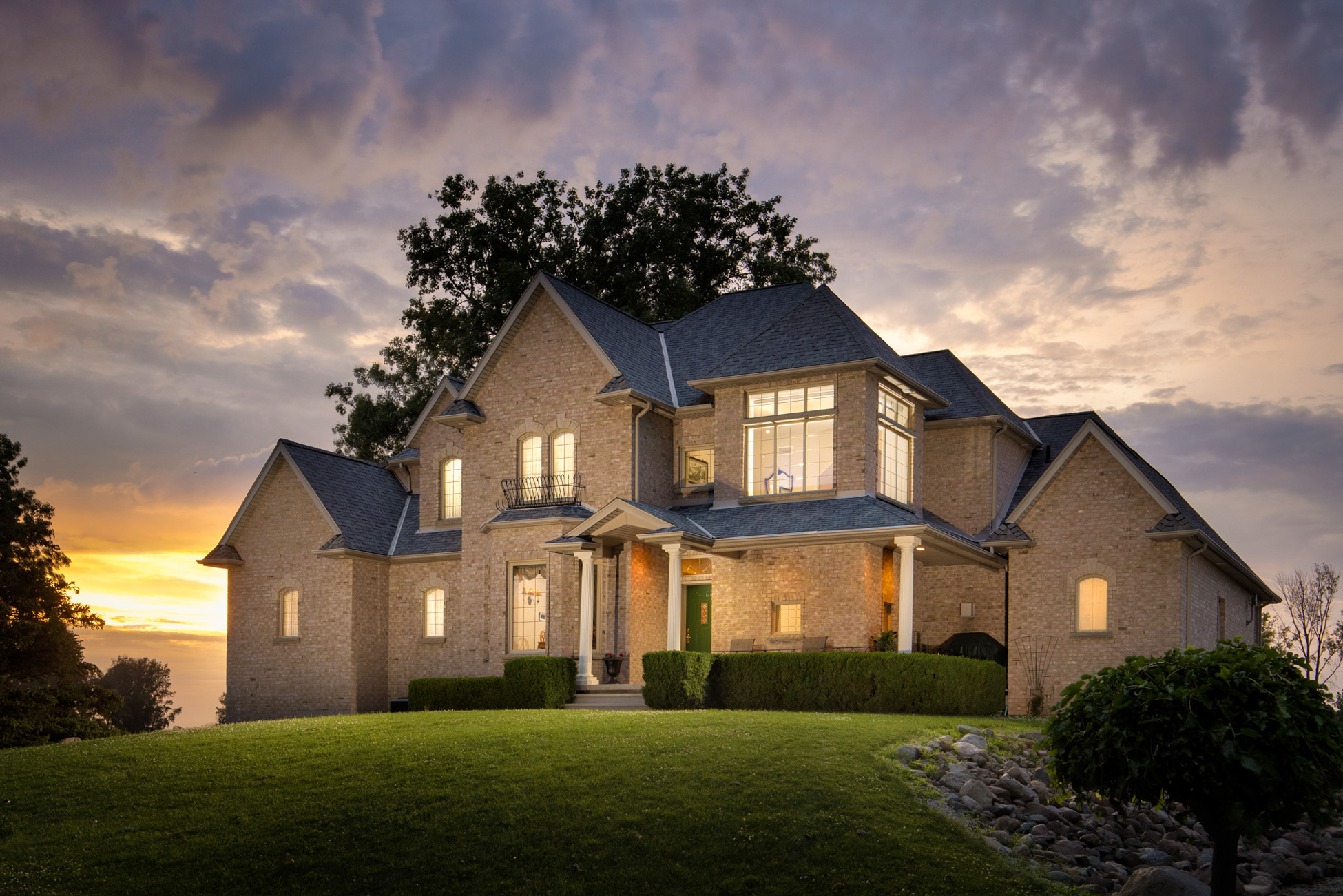 Twilight photo of house front exterior sitting on a small hill, warm lights coming from the windows