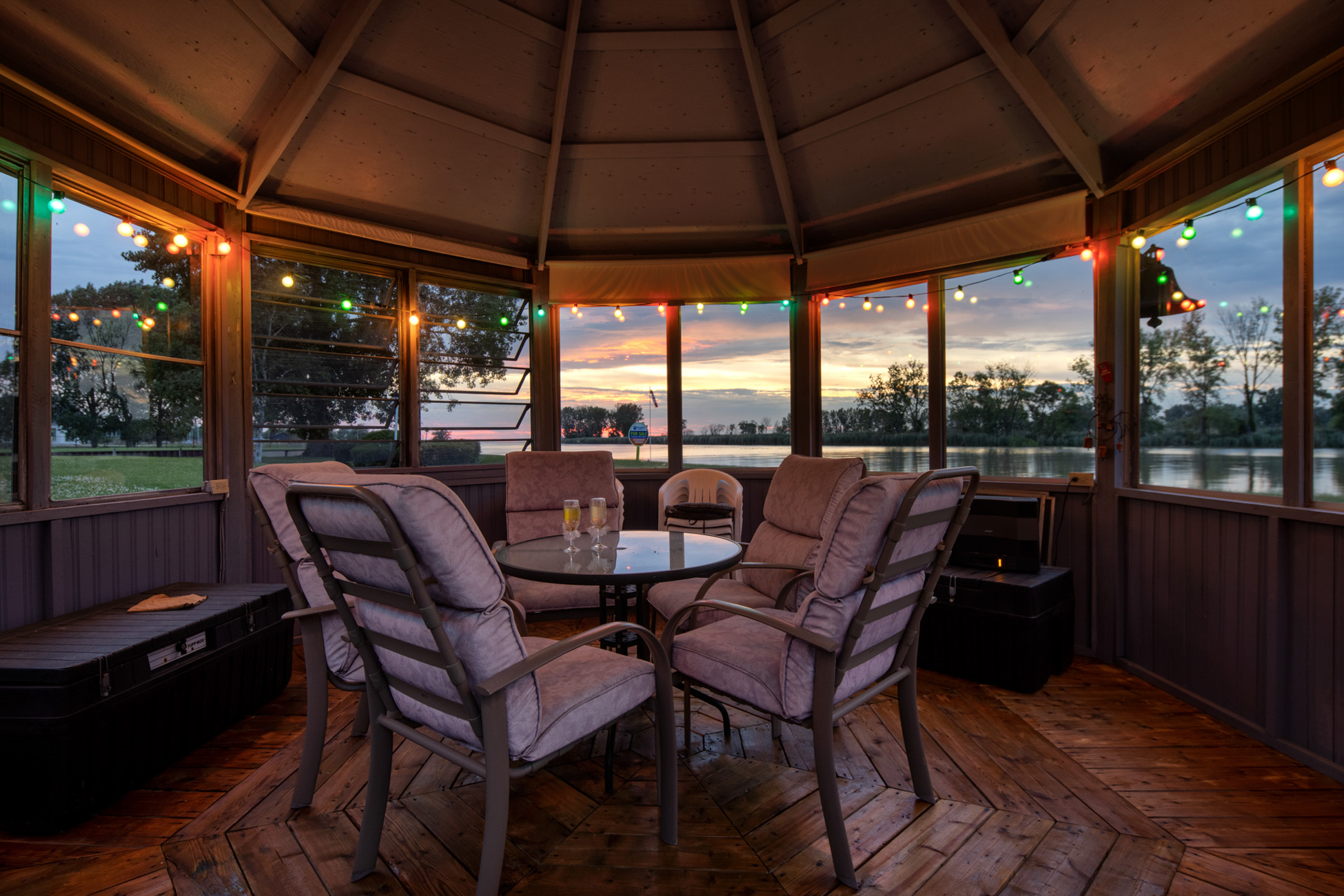 Gazebo with multi-coloured light garlands and patio set overlooking the sunset with water view